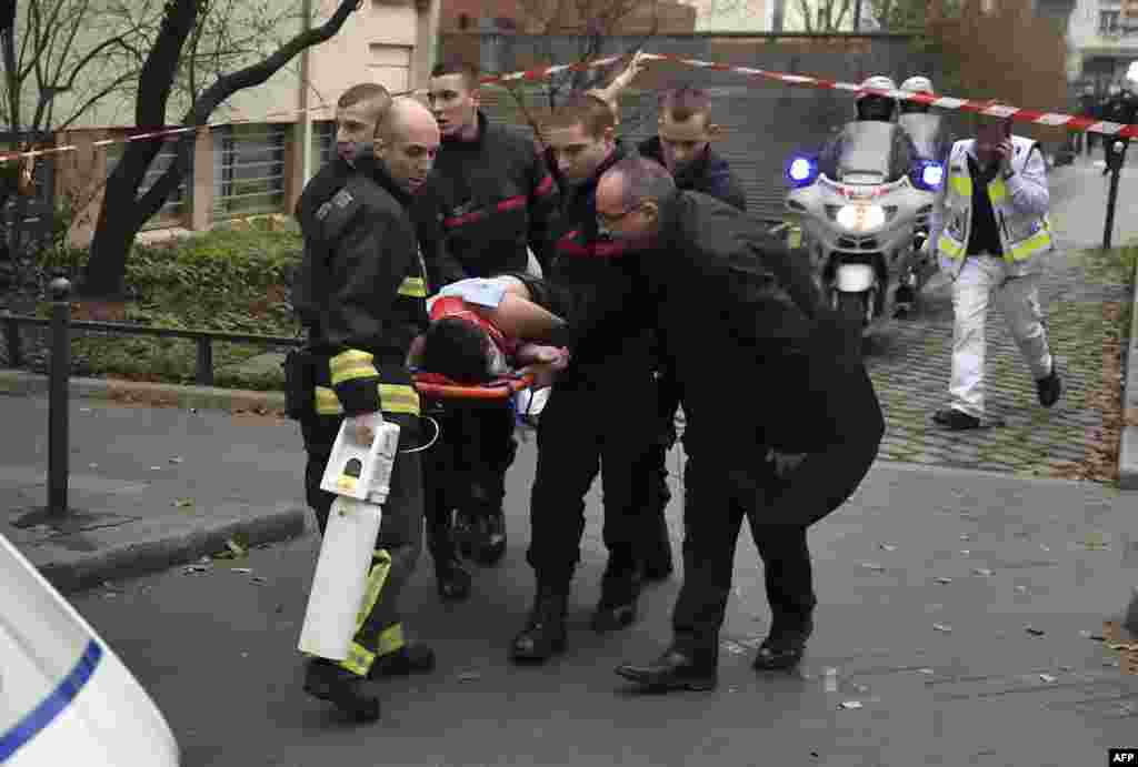 A victim is evacuated on a stretcher outside the publication's offices.