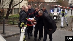A victim is evacuated on a stretcher after armed gunmen stormed the offices of the French satirical newspaper Charlie Hebdo in Paris on January 7.