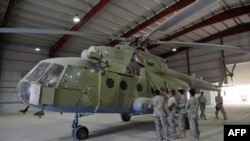 A U.S. Air Force soldier gives explanations to a group of Afghan translators for the Afghan National Army Air Corps on the Russian Mi-17 transport helicopter at a hangar in Kandahar air base in October 2009.