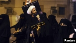 پوستری از شیخ نمر النمر در دستان معترضان شیعه عربستان سعودی