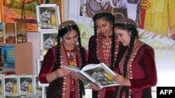 Туркяменські дівчата роздивляються президентську книжку про конярство, ілюстраційне фото