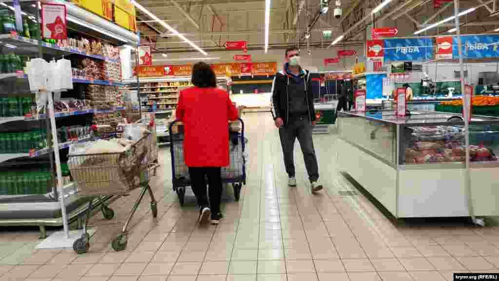 Большинство посетителей внутри гипермаркета носят маски