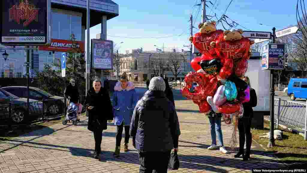 Девушка продает воздушные шары.Средняя цена одного шара в виде сердца составляет 200 рублей (80 грн)