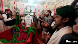 Men say a prayer over the grave of Mumtaz Qadri at the shrine built over his grave outside Islamabad on February 28.