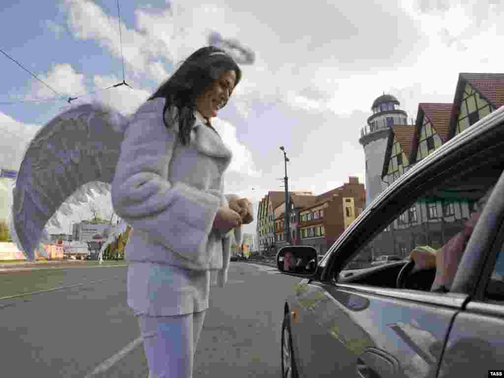 A Russian female traffic police officer dressed as an angel talks to a car driver in central Kaliningrad on the international day to commemorate traffic-accident victims on November 14. (ITAR-TASS/Yelena Nagornykh)