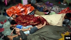 Indian border villagers sleep as they take shelter inside a community hall at RS Pura village, about 25 km from Jammu, the winter capital of Kashmir on October 9, 2014.