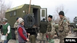 Kazakh soldiers talk to women who are preparing meals for flood victims on March 15, 2010.