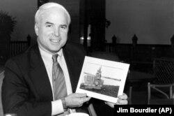 Джон Маккейн с фотографией монумента, который возведен во Вьетнаме в честь его пленения, 18 февраля 1985