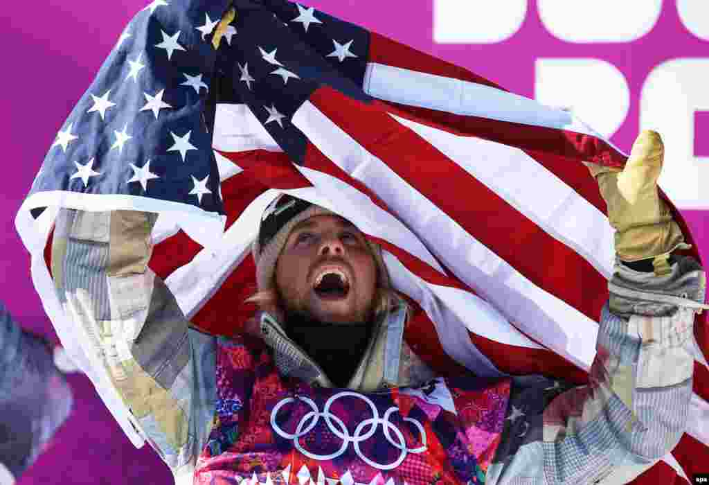 U.S. snowboarder Sage Kotsenburg celebrates winning the games' first gold medal in the men's slopestyle final.