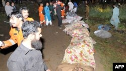 Pakistani rescue workers stand next to the covered remains of victims at the crash site.