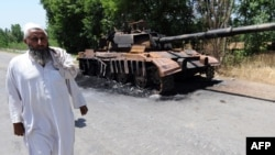 A local man walks past the wreckage of an army tank destroyed by Taliban militants in the troubled Buner district on May 22.