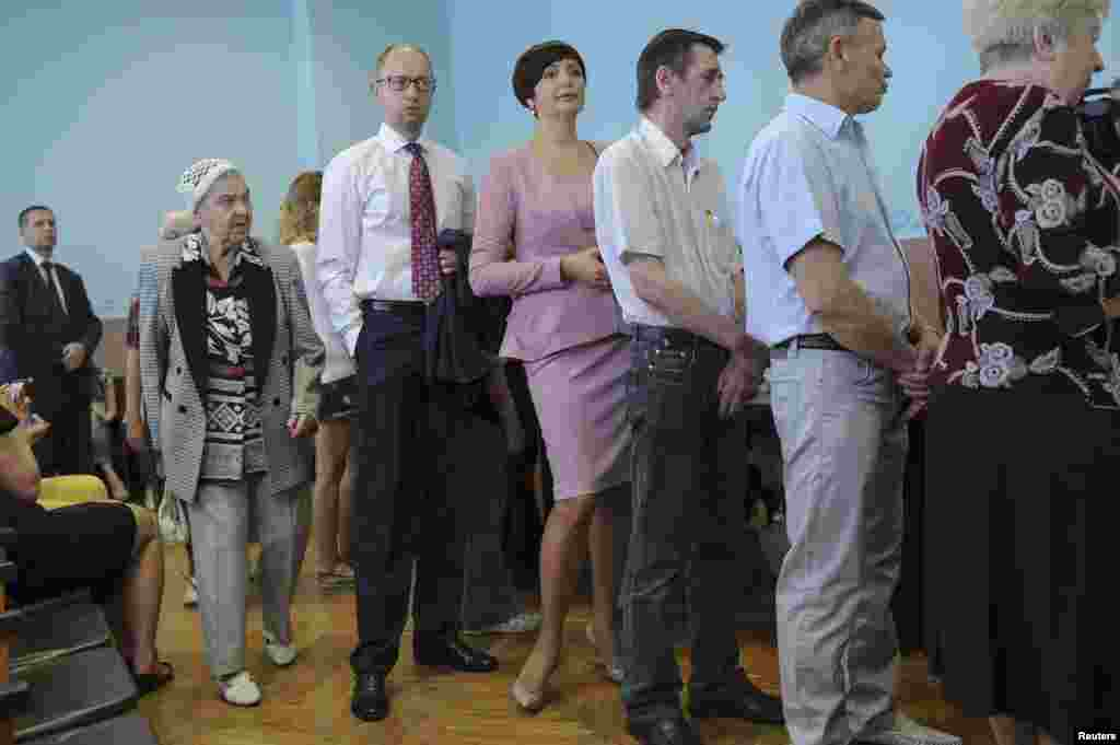 Ukrainian Prime Minister Arseniy Yatsenyuk (3rd left) queues to collect his ballot papers during voting in the presidential election at a polling station in Kyiv on May 25. (Reuters/Andrew Kravchenko)