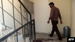 A man walks past bloodstains at the site of the killing of two alleged Al-Qaeda operatives by Pakistani security forces in Karachi in August 18.