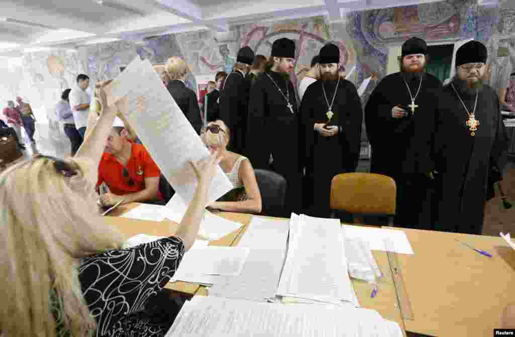 Priests queue to collect their ballot papers before voting at a polling station in the capital, Kyiv.