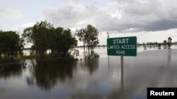 Australia -- A street sign is seen partially covered by floodwaters near Rockhampton, 03Jan2010