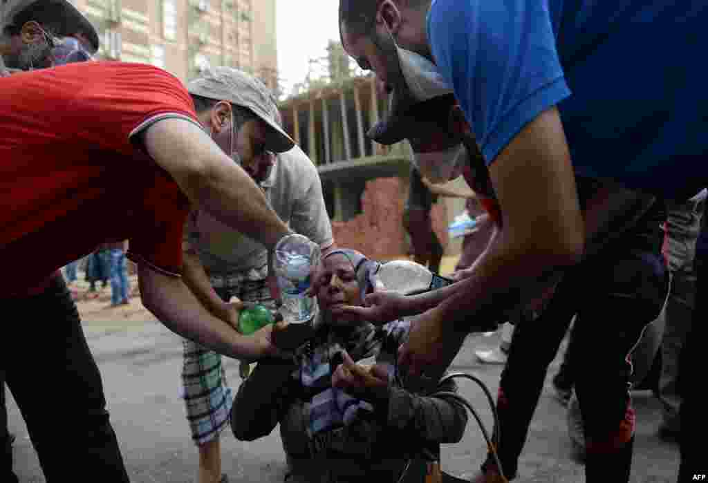 Egyptians help a woman suffering from tear gas exposure.