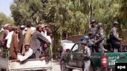 FILE : Men transport the bodies of four civilians killed in an airstrike in Kandahar in 2009.