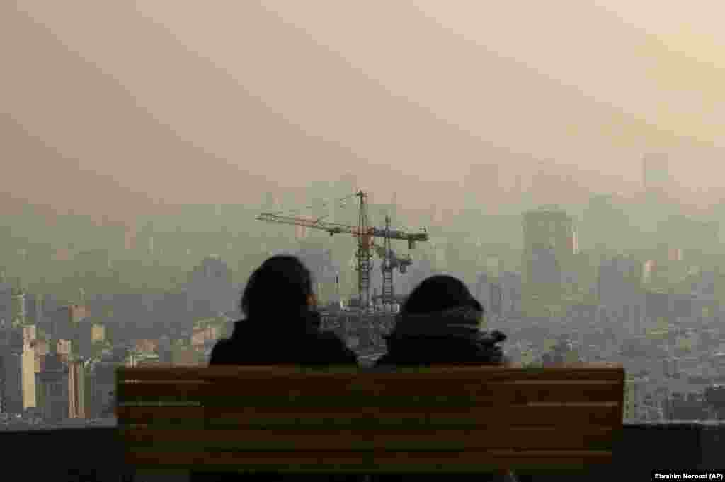 Two Iranians look out at Tehran's smoggy skyline on December 23. (AP/Ebrahim Noroozi)