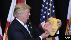 Дональд Трамп с собственной маской в руке во время встречи с избирателями в Сарасоте, штат Флорида 7 ноября 2016 года