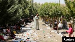 Iraq -- Displaced people from the minority Yazidi sect, fleeing the violence in the Iraqi town of Sinjar, rest as a man stands amongst garbage at the Iraqi-Syrian border crossing in Fishkhabour, Dohuk province, August 13, 2014