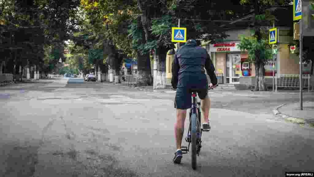 Велосипедист на перехресті в очікуванні зеленого сигналу світлофора
