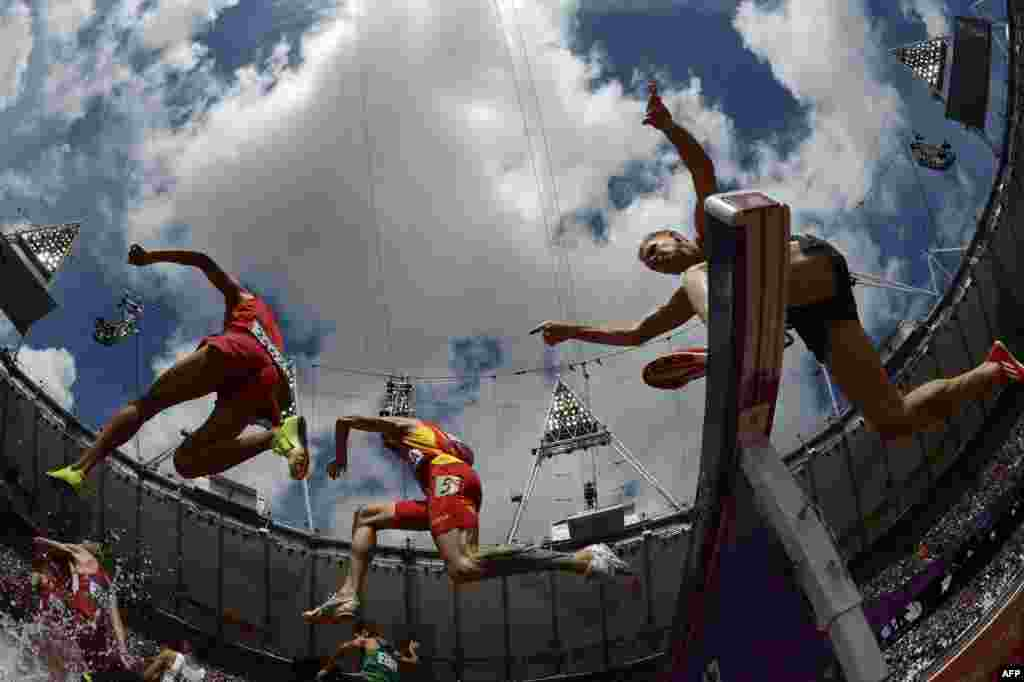 Athletes compete in the men's 3000-meter steeplechase heats in the Olympics track-and-field program. (AFP/Adrian Dennis)