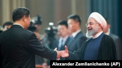 Chinese President Xi Jinping, left, greets Iranian President Hassan Rouhani at the Shanghai Cooperation Organization (SCO) Summit in Qingdao in eastern China's Shandong Province, Sunday, June 10, 2018