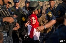 Солдат полицейского спецназа Ирака целует девочку, спасенную в Мосуле. 10 июля 2017 года