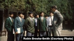 Robin Brooke-Smith talking to students wearing the distinct green blazers of Edwardes College.