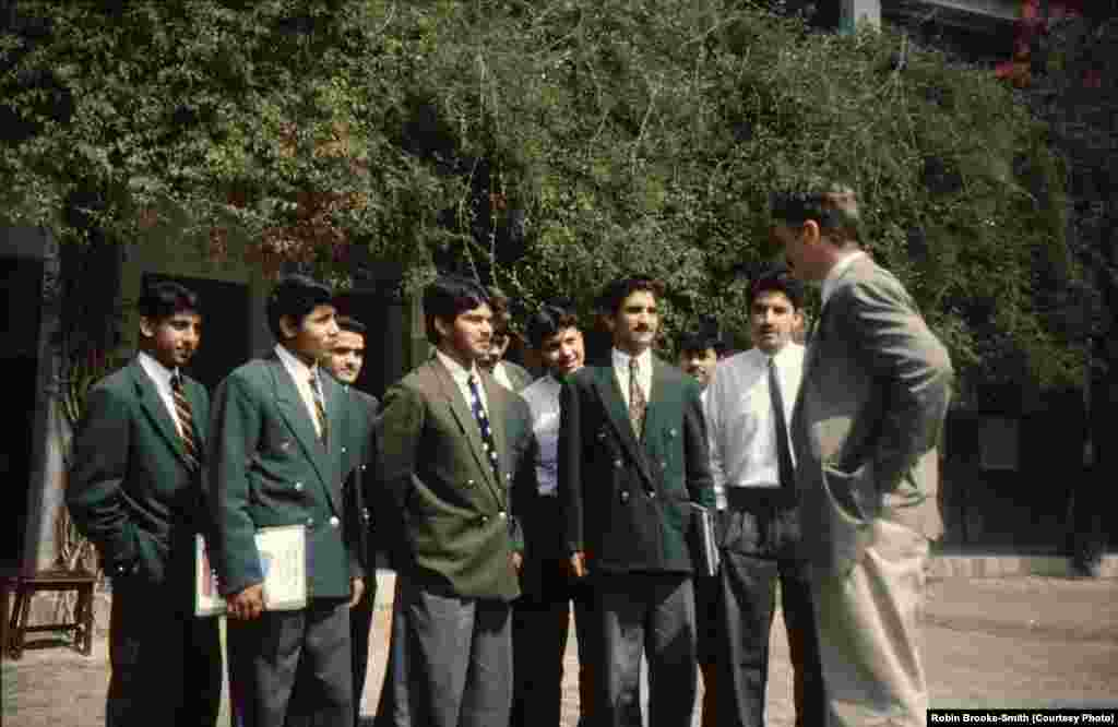 Principal Robin Brooke-Smith talking to students wearing the distinct green blazers of Edwardes College.