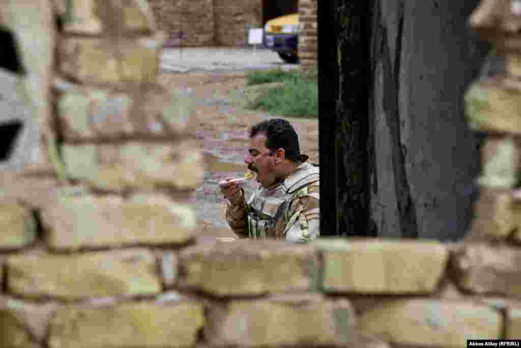 A militiaman takes a lunch break while guarding the Al-Madain, the site of an ancientmetropolis spanning the Tigris River south of Baghdad.