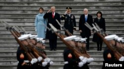 U.S. -- Newly inaugurated U.S. President Donald Trump (in red tie), first lady Melania (L), Vice President Mike Pence and his wife Karen (R) preside over a military parade during Trump's swearing ceremony in Washington, U.S., January 20, 2017.