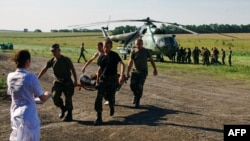Ukrainian soldiers carry a wounded comrade on a stretcher, with a Ukrainian helicopter and other troops in the background, on July 31 in a field near Zaporizhya.