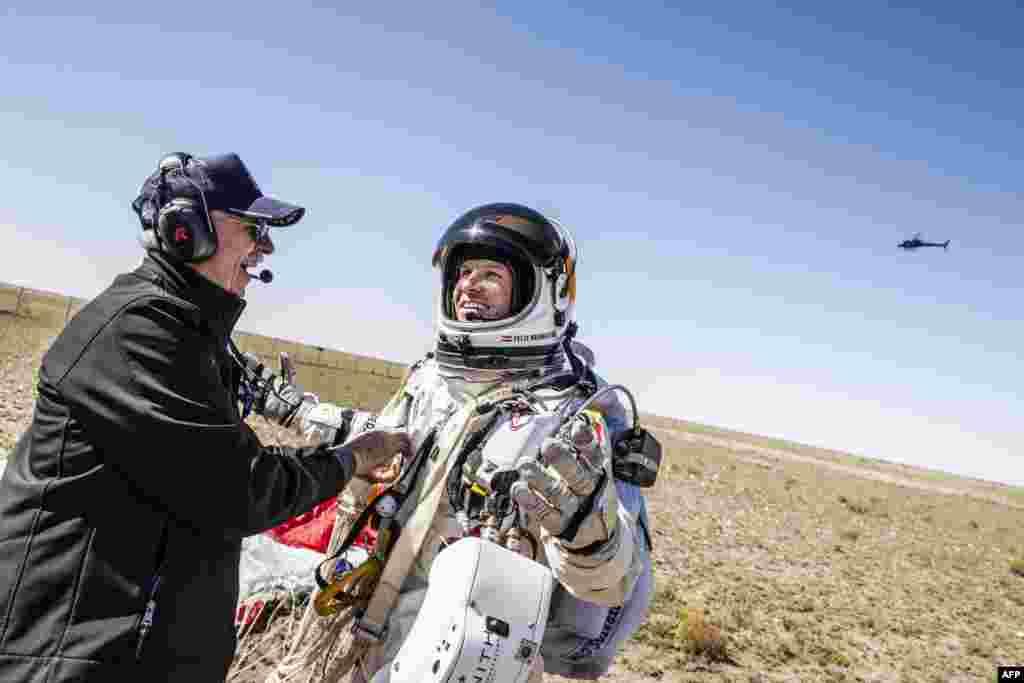 Life support engineer Mike Todd (left) greets Baumgartner after he landed safely.