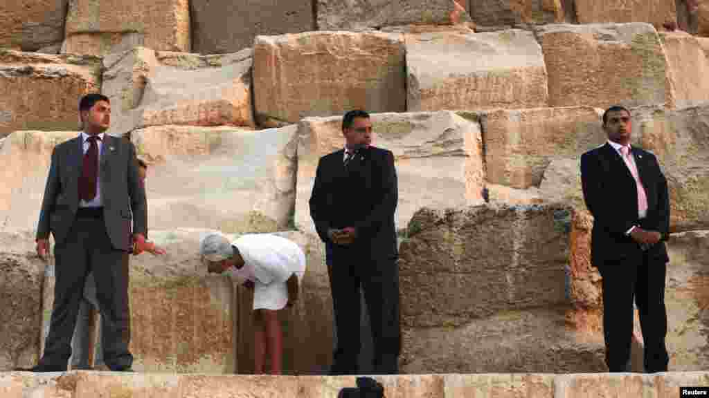 The head of the International Monetary Fund, Christine Lagarde (second from left), inspects some pyramid stones next to security guards while touring Giza, Egypt, on August 22. (REUTERS/Asmaa Waguih)