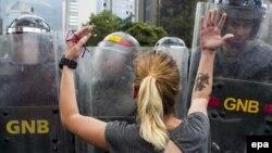 Демонстрантка в районе Каракаса Альтамира пытается говорить с бойцами Национальной Боливарианской гвардии Венесуэлы