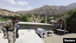 عنصر أمني كردي يتفحص آثار قصف إيراني
