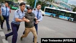 Полиция Олмаота шаҳри марказида митингда қатнашган йигитни ушлаб олиб кетмоқда. 2019, 12 июнь