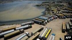 Грузовые автомобили и автоцистерны в пакистанском порту Карачи ожидают возобновления перевозок на север, к афганской границе.