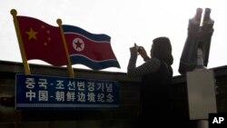 Туристка делает фотографию на смотровой площадке вблизи границы между Северной Кореей и Китаем в Яньбяне