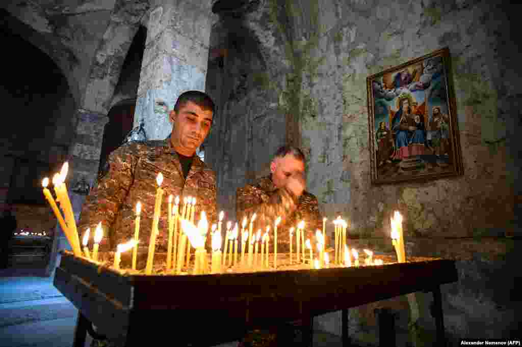 Armenian soldiers light candles as they pay tribute to the dead inside the monastery.