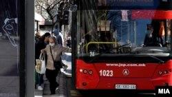 Илустрација - Луѓе со заштитни маски на автобуска постојка во Скопје