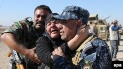 پلیس عراق، مادرش را که از موصل جان به در برده در آغوش میکشد