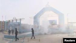 Люди рядом с разрушенной на площади Жанаозена сценой. 16 декабря 2011 года. На этой площади нефтяники простояли более семи месяцев, требуя справедливой оплаты труда.