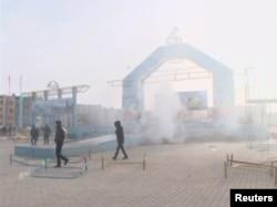 Люди проходят мимо разрушенной сцены на площади в Жанаозене. 16 декабря 2011 года.