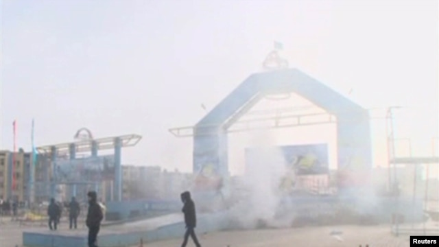 People walk past a destroyed stage in Zhanaozen in this still image taken from a video acquired by Reuters on December 16.