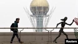 """Астанадағы """"Бәйтерек"""" монументінің жанынан өтіп бара жатқан ер адам."""