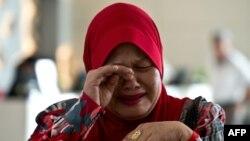 Жоғалған ұшақтағы адамдардың бірінің туысы жылап тұр. Малайзия, 12 наурыз 2014 жыл.
