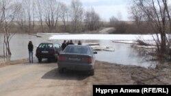 Қызылжар ауданының Новоникольск ауылында су басқан көпірден өте алмай тұрған тұрғындар. Солтүстік Қазақстан облысы, 20 сәуір 2018 жыл.