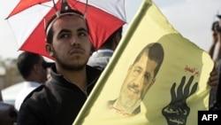 Pristalica zbačenog egipatskog predsednika Mohameda Morsija pred početak suđenja u Kairu